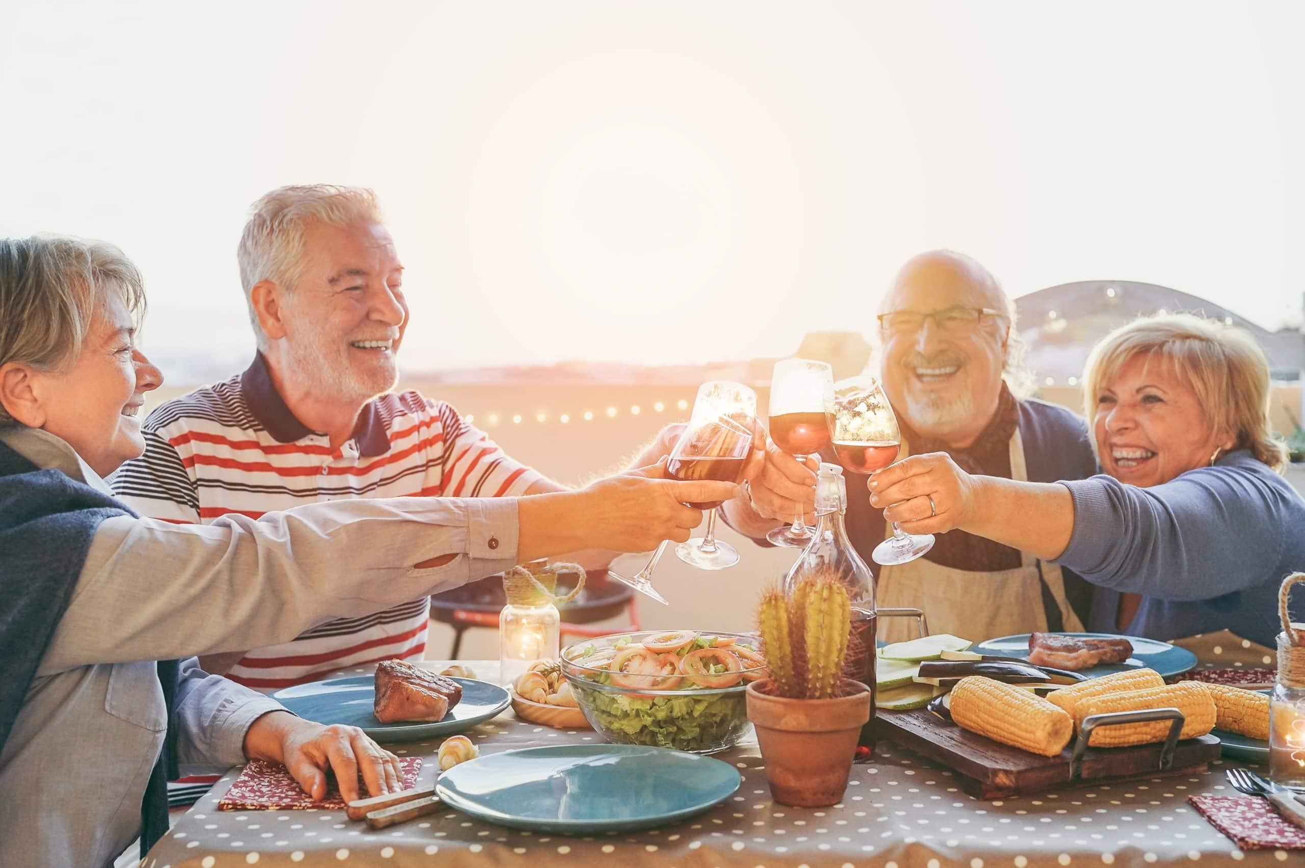 Happy senior friends having fun cheering with red wine at barbecue in terrace  outdoor - Mature people making dinner toasting glasses and laughing together - Friendship and elderly lifestyle concept
